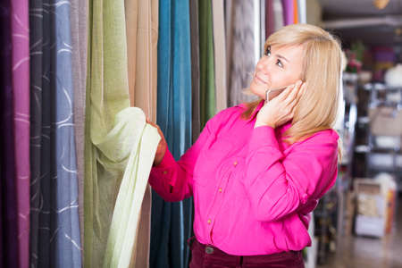 woman choosing curtains and using phone