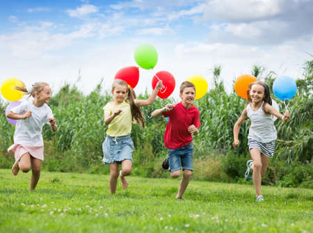children running with air balloons in park .