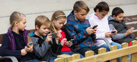 Little boys and girls sitting with tablets outdoor
