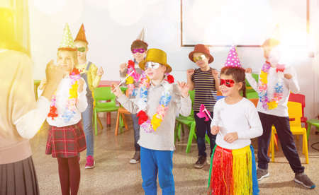 School kids with teacher in festive hats having fun 免版税图像