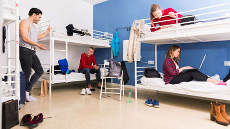 Young men and women friendly interacting while staying in modern comfy hostel