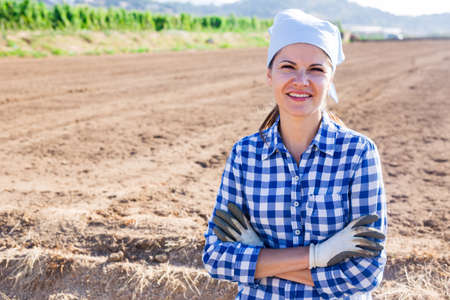 Woman farmer posing outdoors on background of tilled field