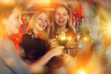 Female friends enjoying wine in night club