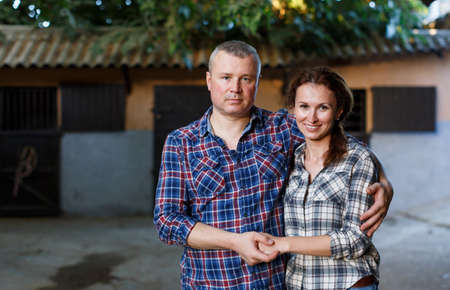 Smiling couple with girth standing at stable outdoor