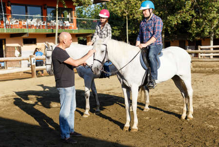 Woman and man with trainer riding horse at farm at summer day