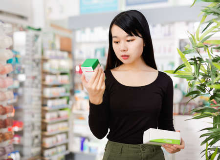 Young chinese female customer looking for right medicine in pharmaceutical store Zdjęcie Seryjne