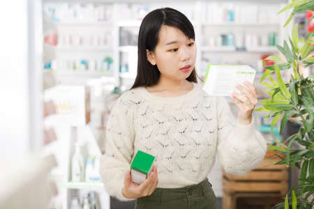 Young serious chinese woman in pharmacy