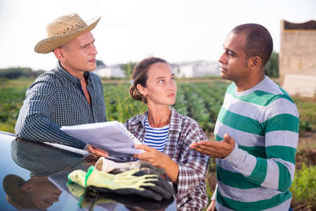 Farmers discussing papers near car on farm Stock Photo
