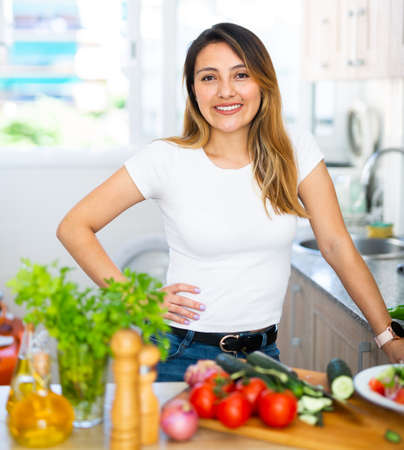 Woman is standing near table and cutting vegetables in the kitchen at the home