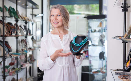 Woman offering to buy fashionable turquoise necklace in the shop of jewelry Zdjęcie Seryjne