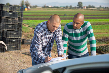 Farmer and worker signing papers near car on farm
