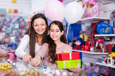 woman and vigorous daughter with gifts and balloons in the shop