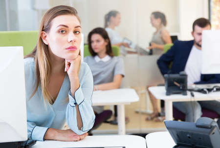 Upset young female foreground in busy open plan office indoor