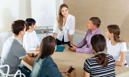 Woman reading out report to colleagues Banco de Imagens
