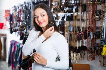 Smiling girl choosing fashionable earrings in the jewelry store 版權商用圖片