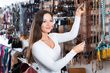 girl consumer choosing necklace