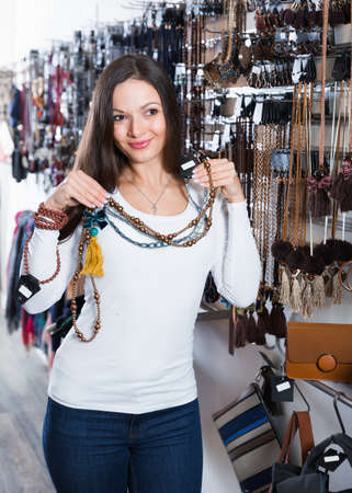 Laughing female choosing new fashion necklace