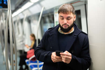 Young man with phone in metro car