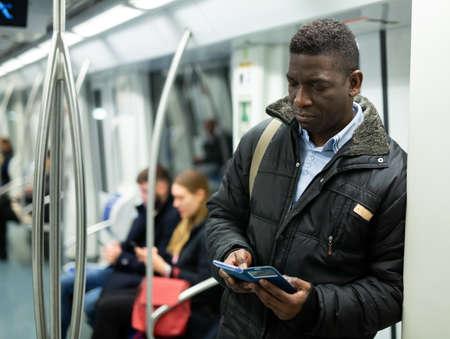 African American man using mobile phone in metro car