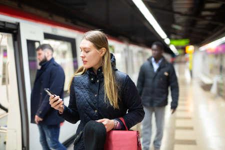 Female passenger with phone waiting for subway train