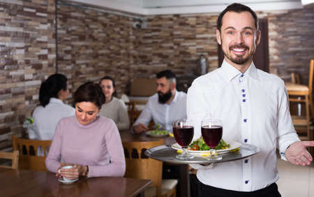 Portrait of adults in middle class restaurant and waiter