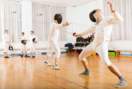 Athletic group practicing fencing techniques