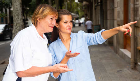 Young woman pointing way to middle aged female