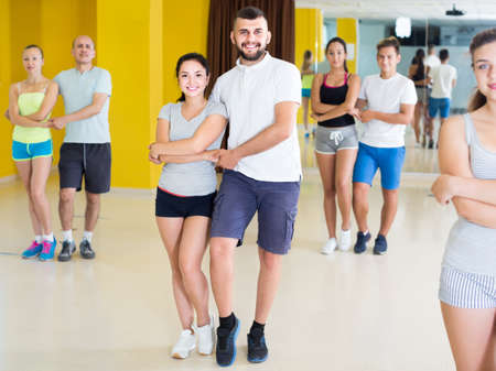 sporty girls and men learning salsa steps