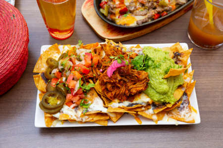 Corn chips nachos with homemade guacamole sauce, meat, cheese