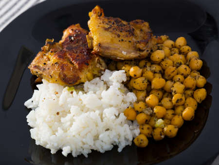 Roasted chicken thighs with chickpeas, rice on black dish Stock fotó