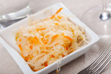 Plate with traditional Russian cabbage sauerkraut on table