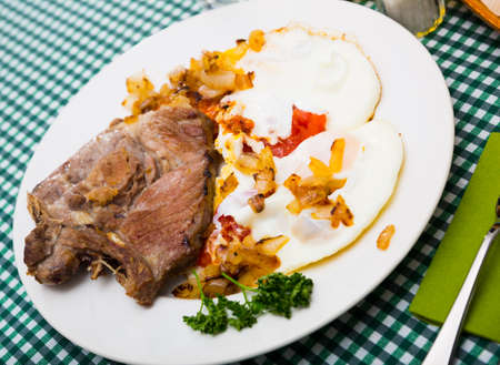 Picture of delicious fried pork with fried eggs at plate, nobody Stock fotó