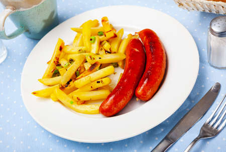 Appetizing sausages with fried potatoes and onion Stock fotó