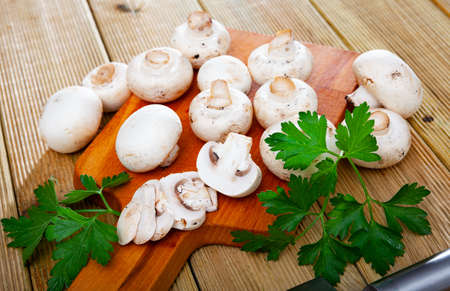 Raw champignons on wooden table