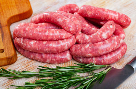Raw meat sausages for frying on wooden desk