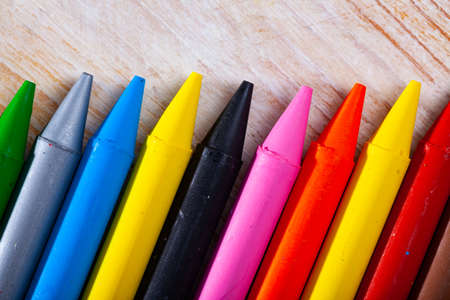 Multicolored crayon pencils on wooden surface