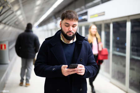 Young man with phone on subway platform