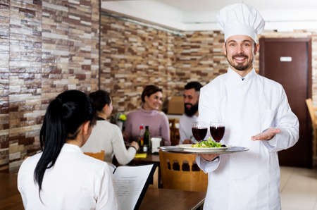 Chef taking care of adults at cafe table