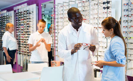 Professional African-American ophthalmologist consulting young woman looking for glasses at optics store Stock fotó