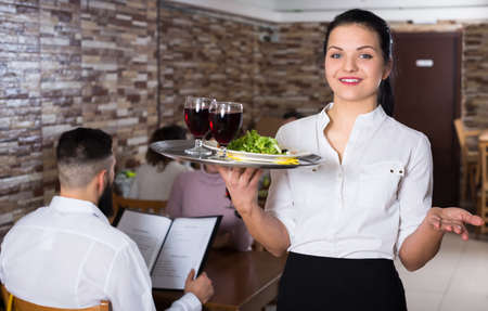 Smiling waitress greeting customers at table Stock fotó