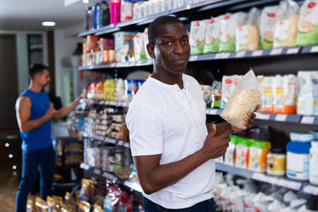 Athletic African looking for necessary food supplements Stock Photo