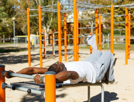 Portrait of active african american man doing leg raises at sports ground