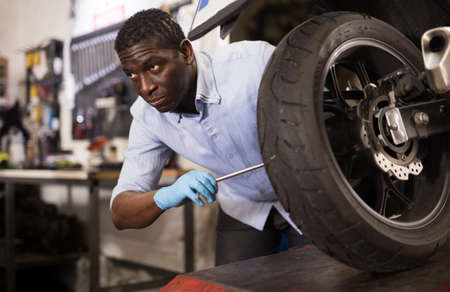 Afro american worker inspects the wheel of a motorcycle