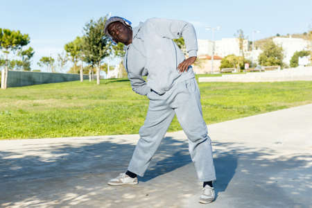 Athletic african american male performs warm-up exercises in park