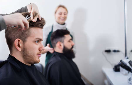 Young clients having their hair cut by hairdressers