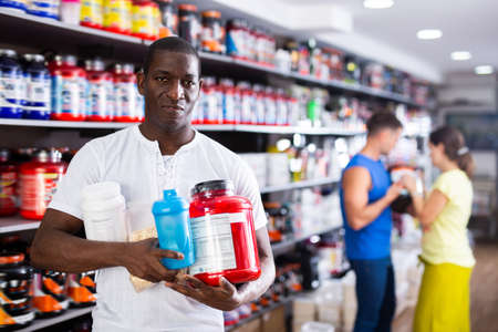 African man with jars of sports supplements