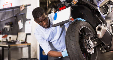 Afro american expert inspects the wheel of a motorcycle Stock fotó