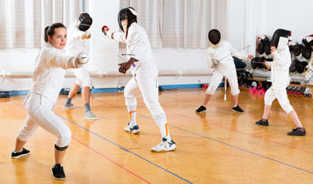 Young woman fencer practicing effective fencing techniques in training room Stock Photo