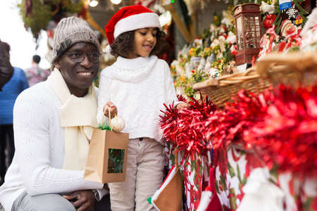 Smiling girl and father with paper bags choosing Christmas toys
