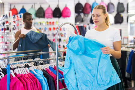 Female buyer choosing sport clothes